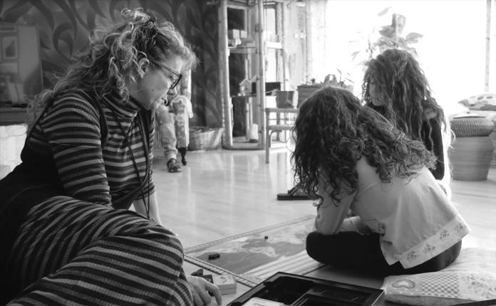 La madre y sus dos hijas se sientan en el suelo mirando un mapa del mundo juntas