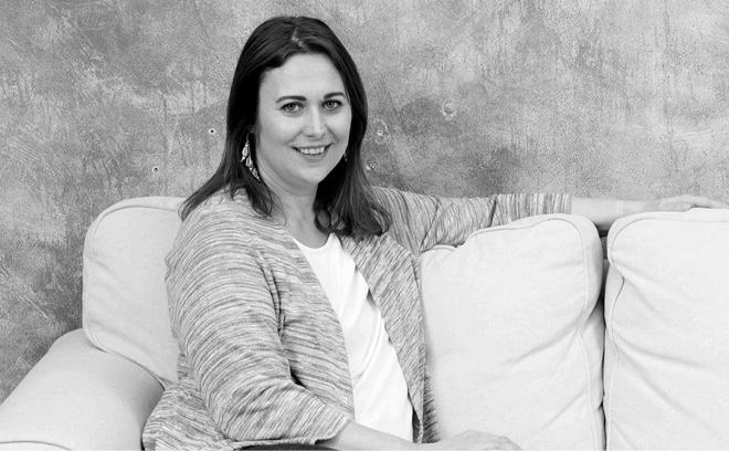 Laura Mascaró sentada en un sofá sonríe a la cámara