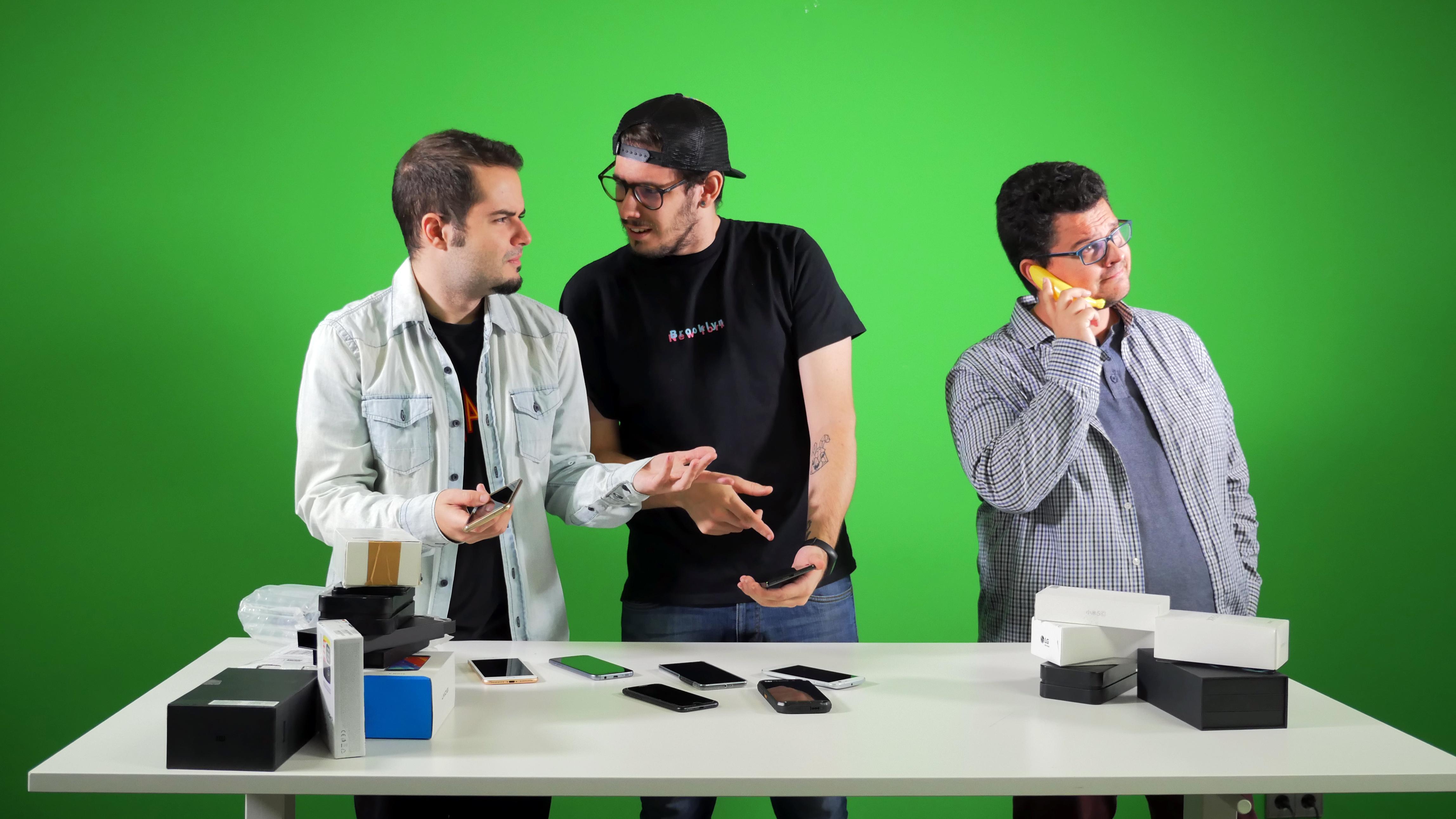 Dos editores prueban móviles para recomendar en el Black Friday, mientras otro usa un plátano para hablar por teléfono