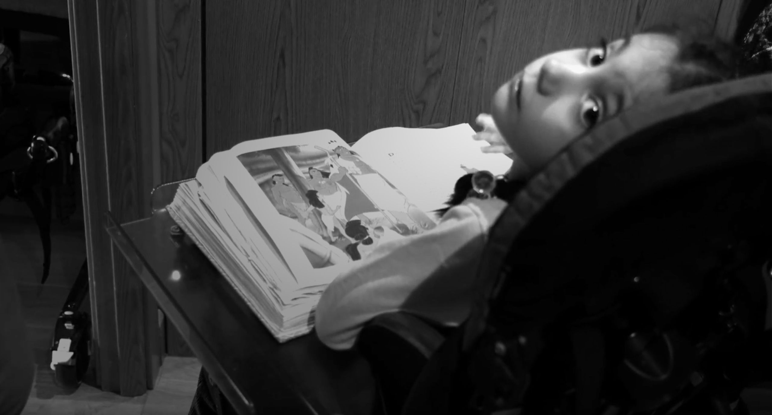 Dulce en su silla de ruedas, con un libro, mirando directamente a la cámara