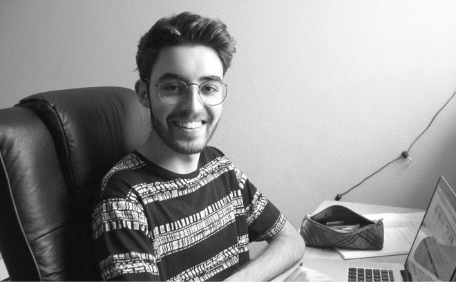 Sergio Belmonte posa sonriente con su ordenador y material escolar
